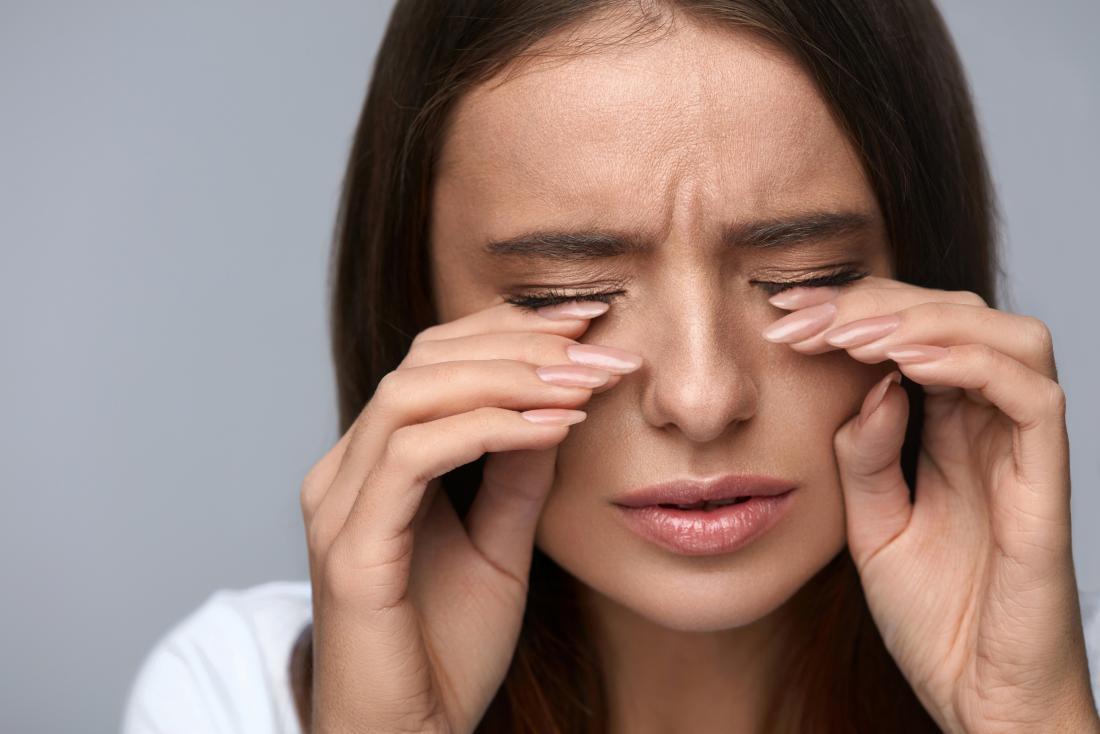 Woman rubbing eyes due to burning eyes