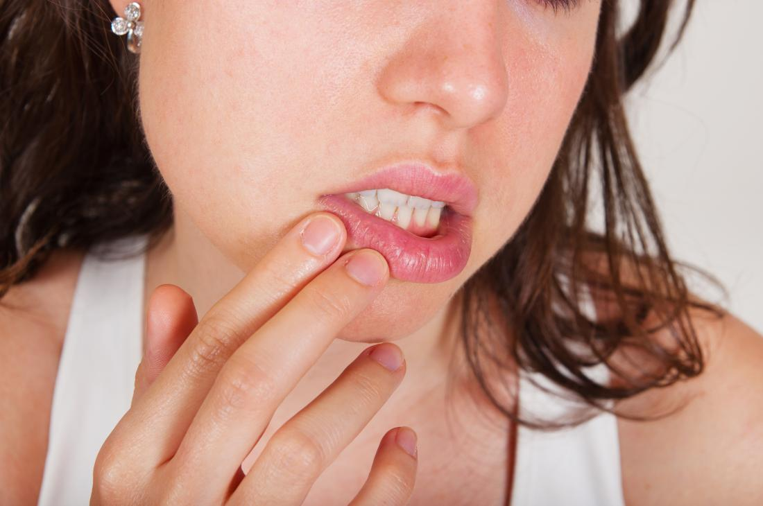 Woman with a citrus allergy holding her mouth